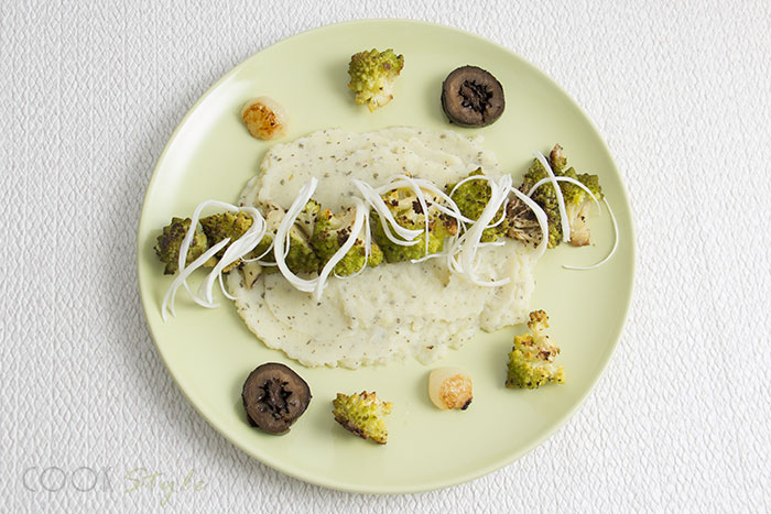 Vegetarian recipe of roasted romanesco broccoli with an herby mash, cheese strings, roasted onions and pickled walnuts