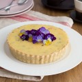 Passion fruit tart decorated with edible pansies