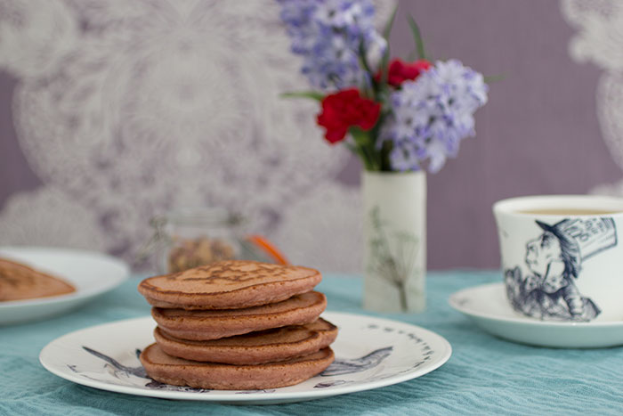Rose pancakes stack. Flowers and tea in the background