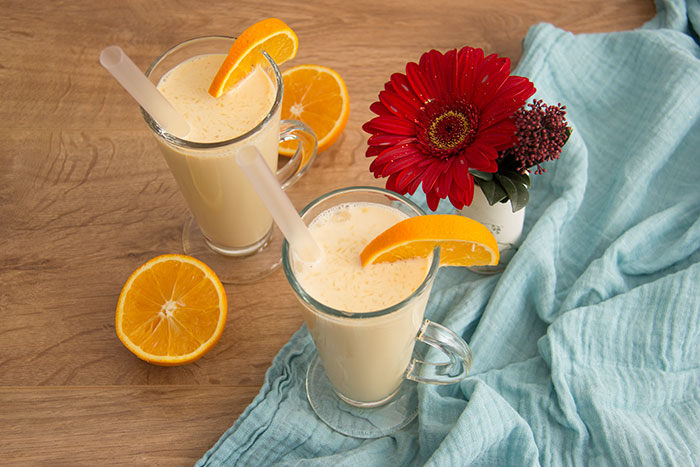 Morir Sonando drink, two glasses decorated with pieces of oranges, a cut orange and a flower