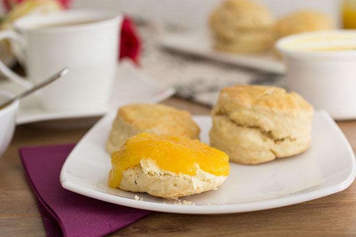 Orange scones, cut and filled with clotted cream and orange jam